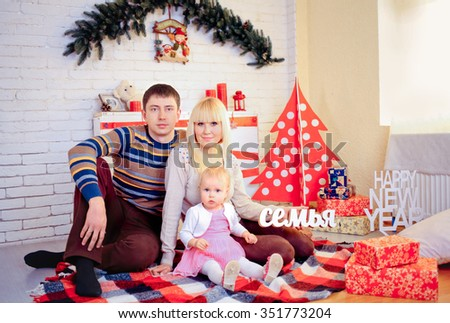 family, christmas, holidays and people concept - happy mother, father and little daughter with gift box sitting on at studio holding in hand the text with the Russian word a family - stock photo