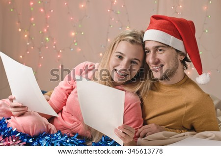 family, Christmas, holidays, love and people concept - happy couple views something on sheets with plaid sitting on sofa at home