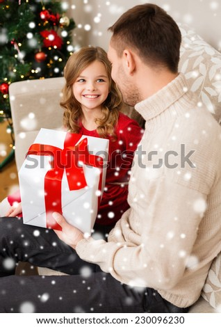 family, christmas, winter holidays, childhood and people concept - smiling father and daughter holding gift box at home