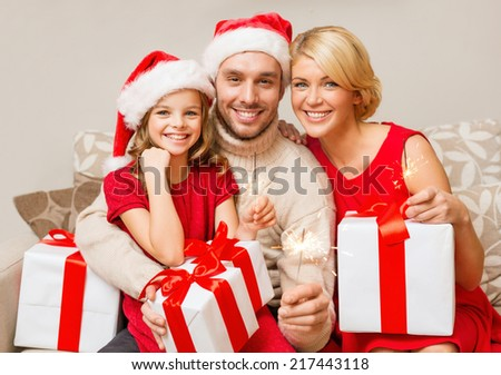 family, christmas, x-mas, happiness and people concept - smiling family in santa helper hats with many gift boxes and bengal lights - stock photo