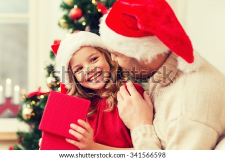family, christmas, x-mas, happiness and people concept - smiling father and daughter in santa helper hats opening gift box - stock photo