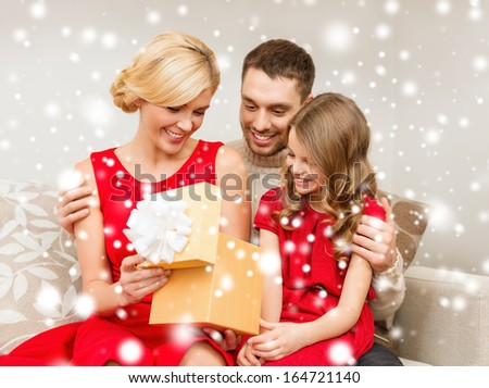 family, christmas, x-mas, winter, happiness and people concept - happy family opening gift box - stock photo