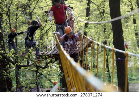 Family climbing rope at the adventure park - stock photo