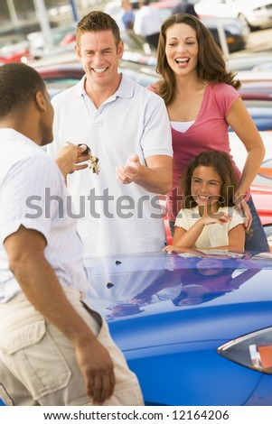 Family collecting new car from dealer