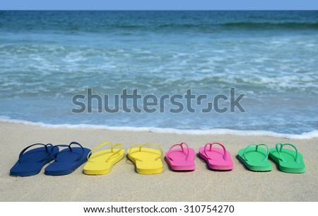 family colorful flip flop sandals on on the beach - stock photo