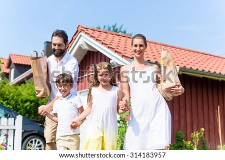 Family coming home from shopping groceries carrying bags
