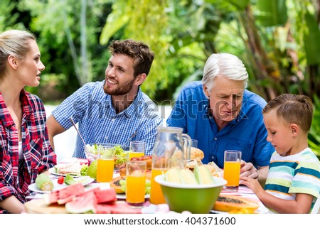 Family communicating during breakfast at yard - stock photo