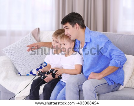 Family concept. Father with sons are playing video games in the room - stock photo