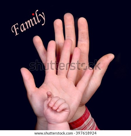 Family concept.  Hands of father, mother and baby, on black background.