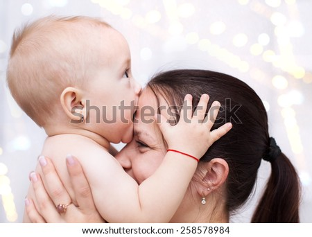 Family concept. Happy young mother playing with baby - stock photo