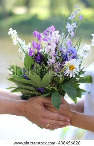 Family concept. Man's hands gives his wife a bouquet of wildflowers.  Men's hands holding woman's hands. - stock photo