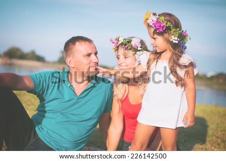 Family concept. Portrait of a happy family of three having fun together outdoors - stock photo