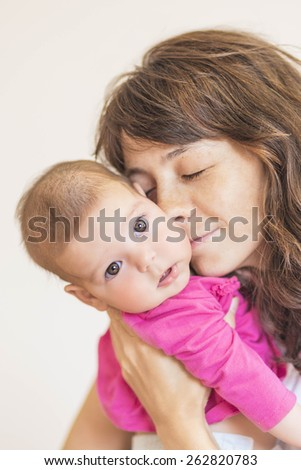 Family Concept: Portrait of Young Mother Taking Care of Her Little Newborn Infant Baby Indoors. Vertical Image Composition