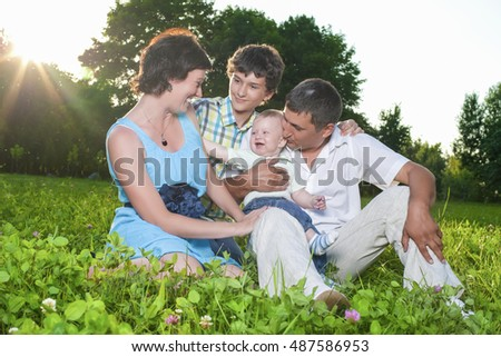 Family Concepts. Young Caucasian Family of Four People Posing Together Outdoors in Park. Sitting Embraced. Horizontal Image