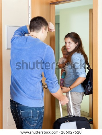 Family conflict. Sad husband against wife with child in living room - stock photo