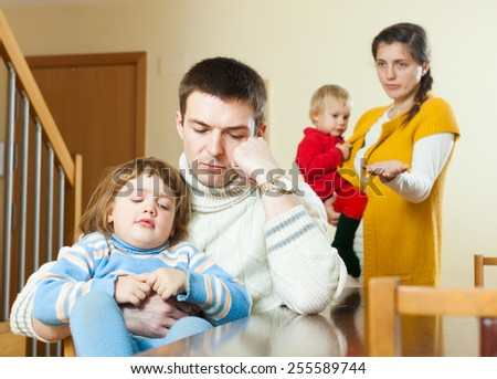 Family conflict. Sad ordinary man listening to woman at home - stock photo