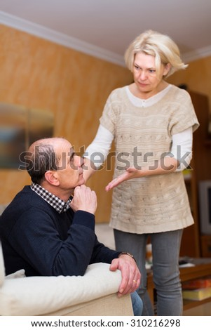 Family conflict. Senior couple after quarrel in living room at home  - stock photo