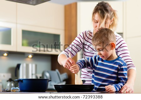 Family cooking in their kitchen � mother and sun cooking spaghetti - stock photo