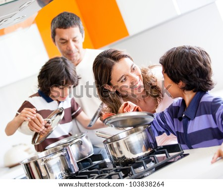 Family cooking together in the kitchen and looking happy - stock photo