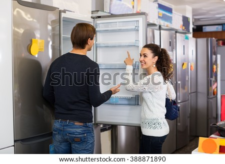 family couple buying domestic refrigerator in supermarket