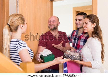 Family couple receiving visitors with a gifts in the home  - stock photo