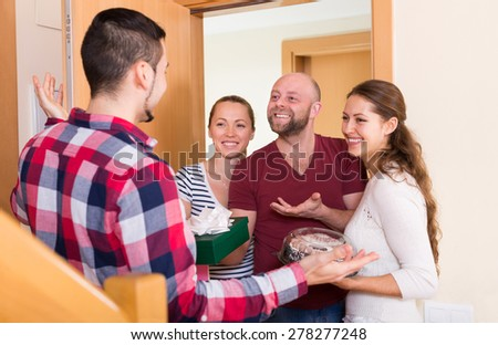 Family couple receiving visitors with the gifts at the home  - stock photo