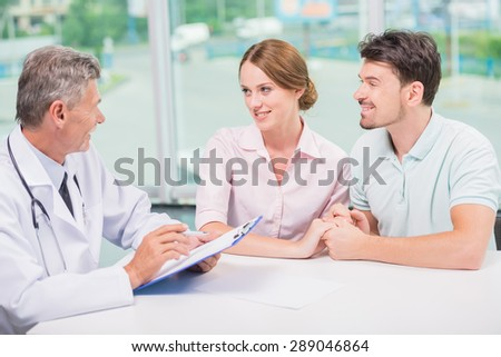 Family couple sitting in doctor's office at consultation. - stock photo