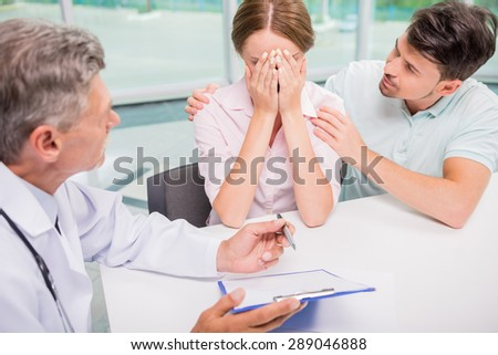 Family couple sitting in doctor's office at consultation. Man comfort his woman. - stock photo