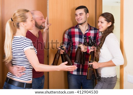 Family couple welcoming american visitors with beer bottles at home - stock photo