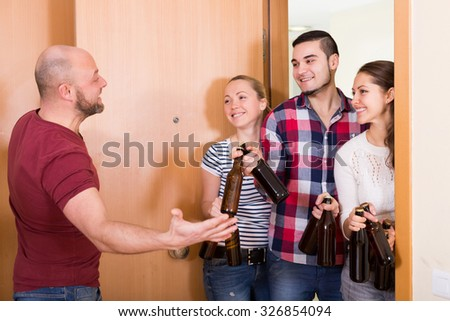 Family couple welcoming happy russian visitors with beer bottles at home