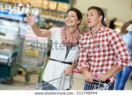 Family couple with trolley cart in meat grocery supermarket during weekly food shopping - stock photo