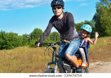 Family cycling, father with happy kid riding bike outdoors  - stock photo