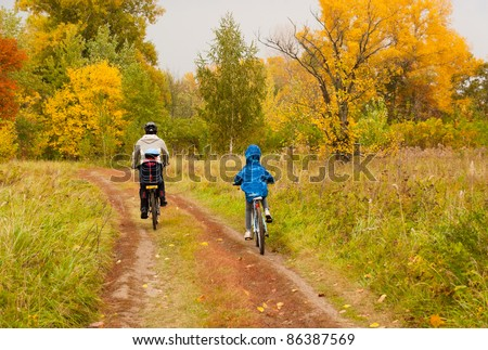 Family cycling outdoors, beautiful golden autumn in park - stock photo