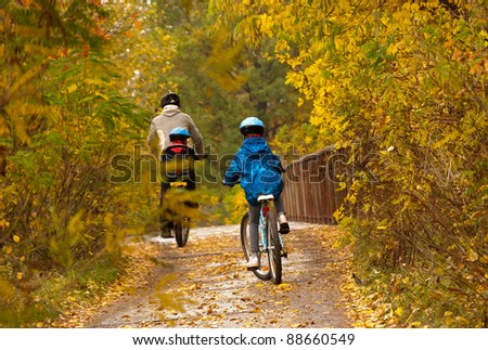 Family cycling outdoors, golden autumn in park. Father with kids on bicycles