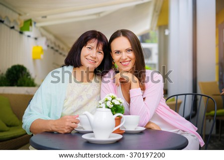 Family day. Aged woman and her adult daughter drinking tea at cafe. - stock photo