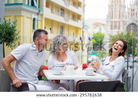 Family day. Senior couple and their adult daughter talking and laughing while sitting in sidewalk cafe. - stock photo
