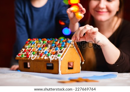 Family decorating gingerbread house on Christmas eve. Focus on house - stock photo