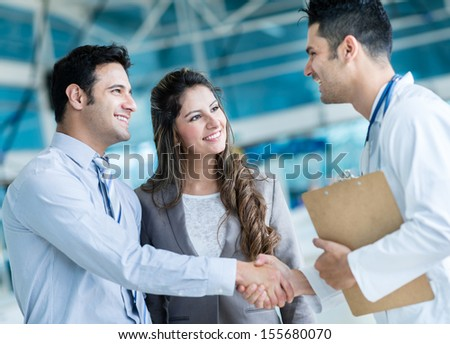 Family doctor handshaking a couple at the hospital  - stock photo