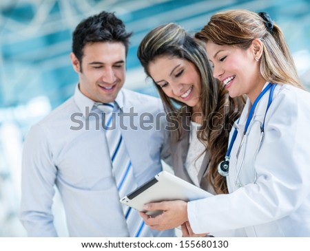 Family doctor with a happy couple at the hospital  - stock photo