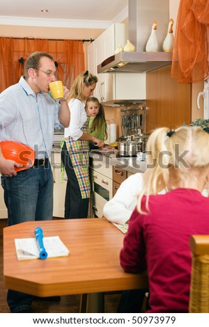 Family doing their breakfast routine in the morning, dad is ready to start to work - stock photo