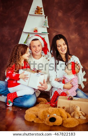 Family dressed for Christmas eve plays with children on the floor