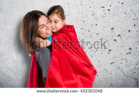 Family dressed like superhero over grey background - stock photo