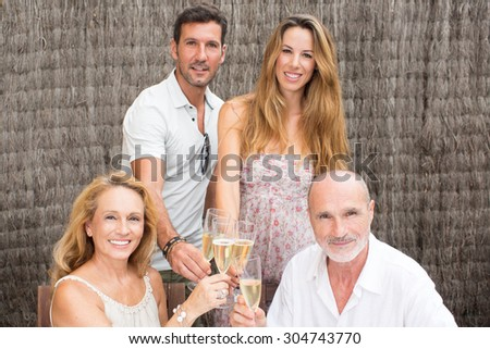 Family drinking champagne in garden - stock photo