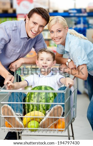 Family drives cart with food and boy sitting there with watermelon. Concept of fresh and healthy food and consumerism