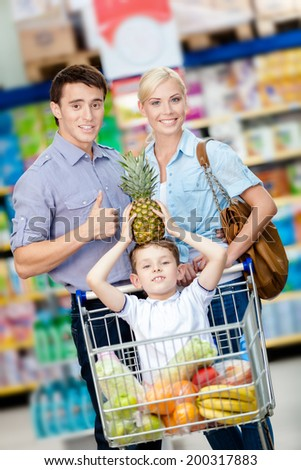 Family drives shopping trolley with food and son sitting there with pine apple on head. Concept of fresh and healthy food and consumerism