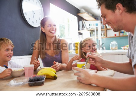 Family Eating Breakfast At Kitchen Table - stock photo