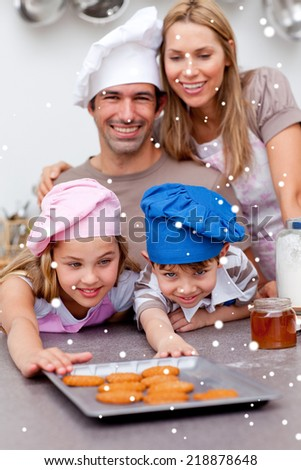 Family eating cookies after baking with snow falling - stock photo