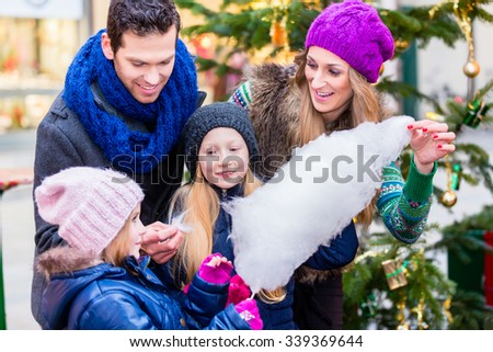 Family eating cotton candy on Christmas market - stock photo