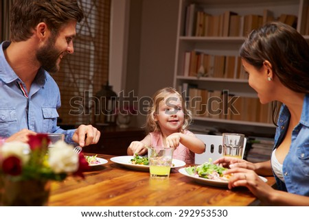 Family eating dinner at a dining table - stock photo