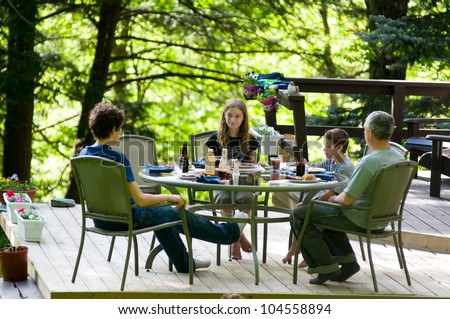 family eating dinner outdoors on a deck